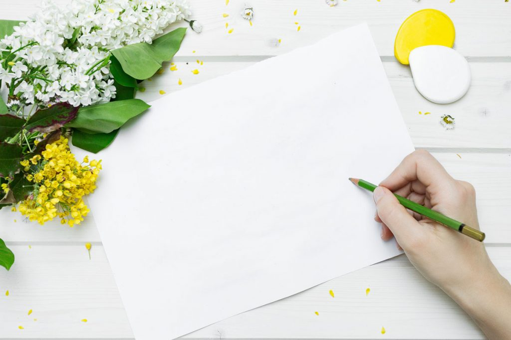 image of hand starting to write in journal
